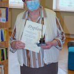 Walentyna Kuszpa, laureatka pierwszego miejsca kategorii dla dorosłych trzymająca odebraną statuetkę Złote Pióro Wójta Gminy Wyryki oraz pamiątkowy dyplom