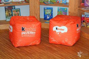 Zdjęcie przedstawia dwie czerwone pufy z logiem Kinder Mleczna Kanapka Przerwa na Wspólne Czytanie