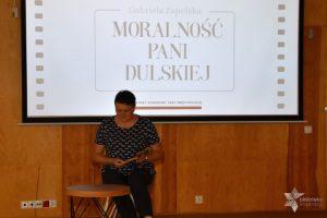 """Uczestniczka wydarzenia czyta fragment utworu """"Moralność pani Dulskiej """" podczas Narodowego Czytania."""