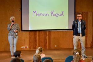 Spotkanie autorskie dla dzieci z Marcinem Koziołem, na scenie Dyrektor GBP w Wyrykach Pani Hanna Czelej wita dzieci.